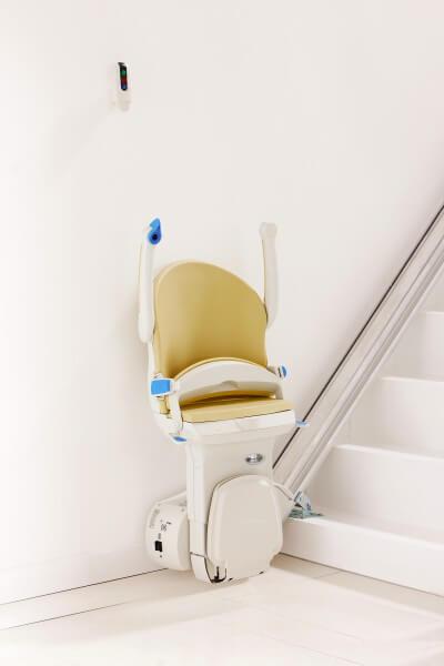 SANIMED 10 plus Sitzlift für gerade Treppen in Startposition in einem weißen Treppenhaus