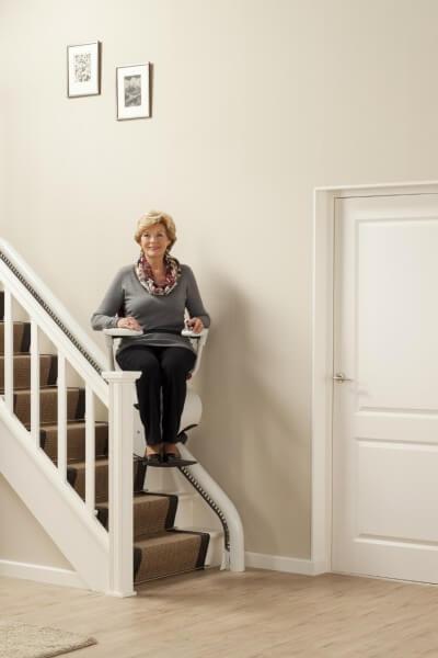 Person fährt mit dem Treppenlift für schmale Treppen