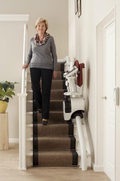 Treppenlift für kurvige Treppen, Treppenlift steht zusammengeklappt in der Mitte der Treppe