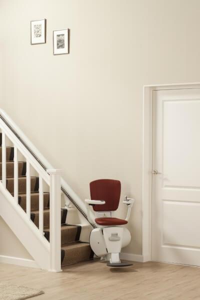 SANIMED 70 Treppenlift für kurvige Treppen, Treppenlift in Startposition am Treppenanfang in einem schönen Wohnzimmer