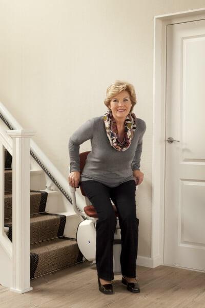 Treppenlift für schmale Treppen, Person setzt sich auf den Treppenlift