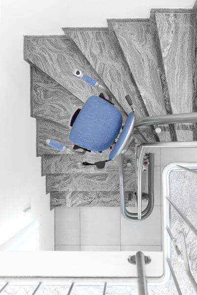 Treppenlift für kurvige Treppen, blaues Polster, von oben, Kurve