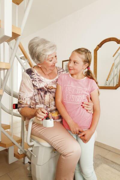 Treppenlift für kurvige Treppen, Großmutter und Kind sitzen