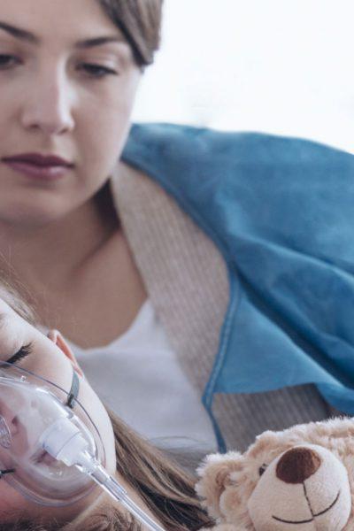 Wer hilft bei Seltenen Erkrankungen - Betreutes Kind mit Atemmaske im Krankenhausbett