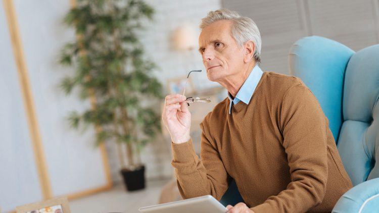 Smart Home und Sicherheit - Senior mit Brille und Tablet in der Hand denkt nach