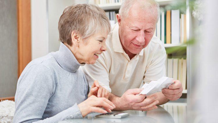Was Sie als Rentner bei der Steuererklärung beachten müssen - Älteres Paar mit Taschenrechner bei der Durchsicht ihrer Belege