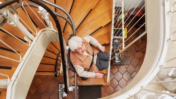 Stiftung Warentest zum Treppenliftkauf - Ältere Frau fährt mit Sitzlift die heimische Treppe hinauf