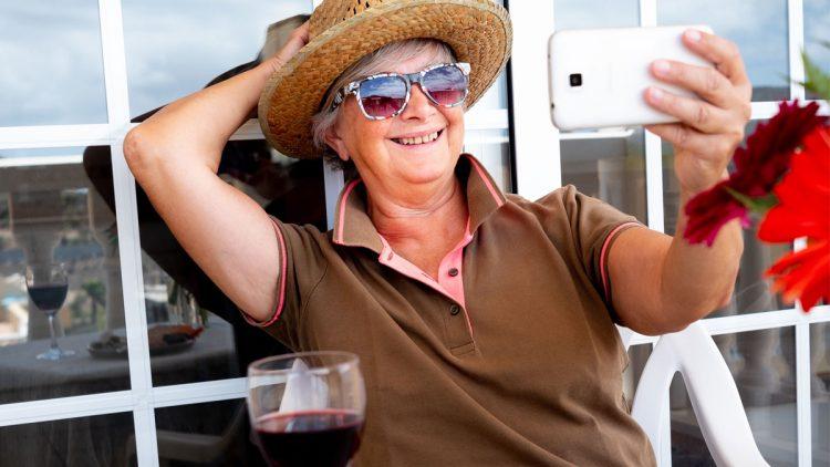 Tipps für Senioren gegen den Corona-Blues - Ältere Frau mit Rotwein macht ein Selfie auf dem Balkon
