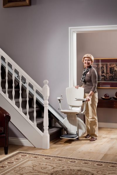 Premium Treppenlift für gerade Treppen Frau steht neben Treppenlift