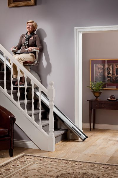 Premium Treppenlift für gerade Treppen Frau fährt glücklich mit Treppenlift