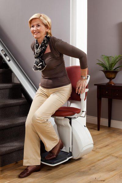 Premium Treppenlift für gerade Treppen Frau steigt aus Treppenlift