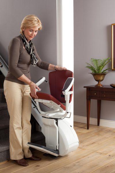 Premium Treppenlift für gerade Treppen Frau klappt Treppenlift zusammen
