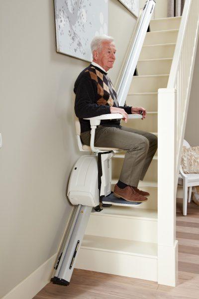 Premium Treppenlift für gerade Treppen Mann fährt die Treppe hinauf