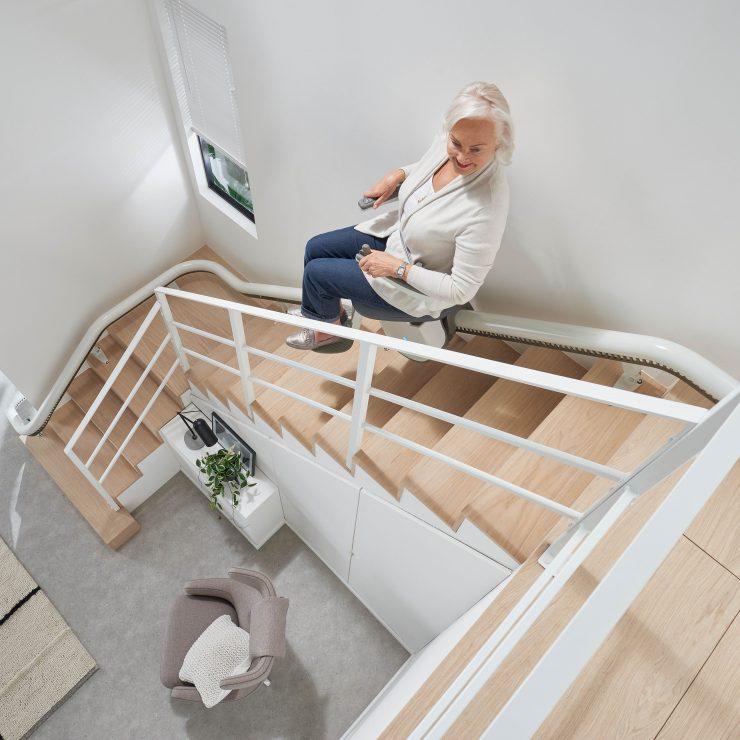 Sicht auf Person und SANIMED 70 EXTRA Treppenlift für kurvige Treppen