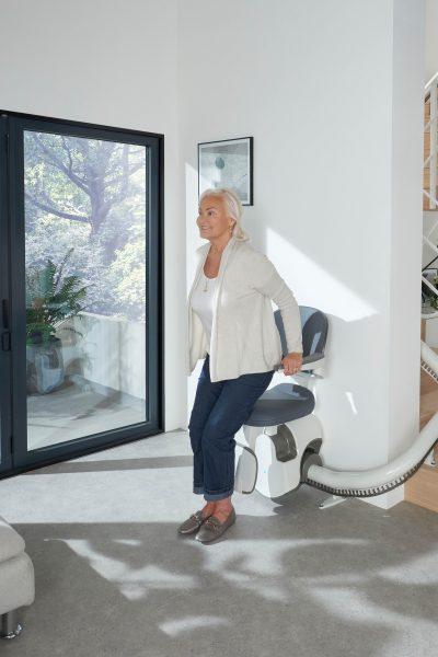 Frau setzt sich auf den SANIMED 70 EXTRA Treppenlift für kurvige Treppen