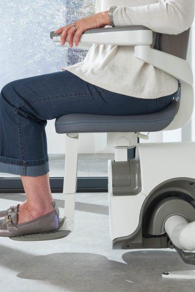 Seitenansicht SANIMED 70 EXTRA Treppenlift für kurvige Treppen mit sitzender Person
