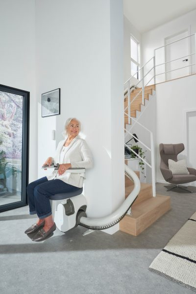 Frau benutzt den SANIMED 70 EXTRA Treppenlift für kurvige Treppen