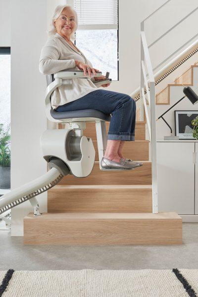 SANIMED 70 EXTRA Treppenlift für kurvige Treppen in Benutzung mit Frau