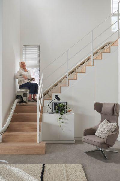 Parkposition auf der Treppe mit Person und SANIMED 70 EXTRA Treppenlift für kurvige Treppen