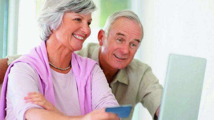 Älteres Paar vor dem Laptop - Antrag für einen Treppenlift-Zuschuss bei der Pflegekasse