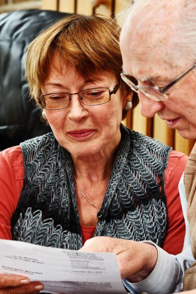 Älterer Mann mit Tochter beim gemeinsamen Lesen der Post