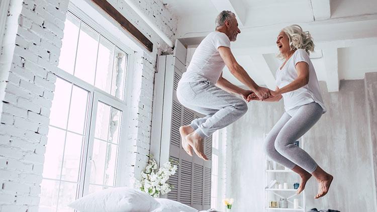 Vom Glück später Liebe - Älteres Paar macht gemeinsame Luftsprünge im Bett