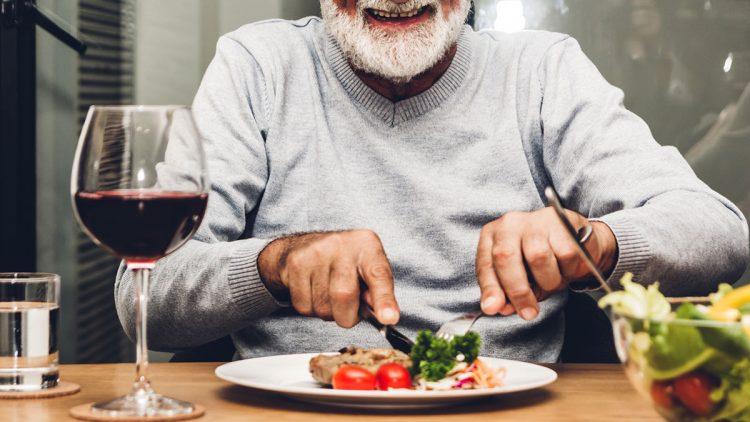 Wie Sie den richtigen Anbieter für Essen auf Rädern findern - Mann beim Essen mit einem Glas Rotwein