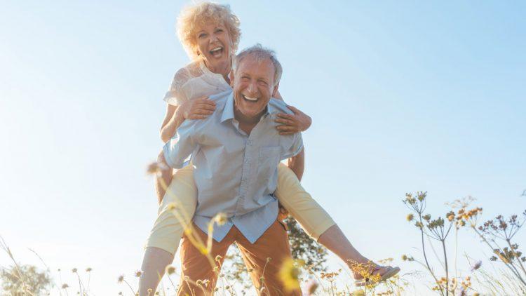 Muskelverspannung, Hexenschuss und Bandscheibenvorfall - Senior trägt auf einer Wiese lachend eine Frau Huckepack