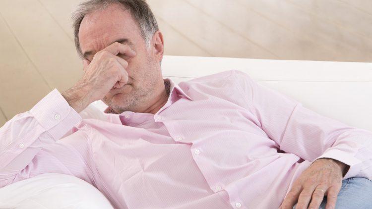 Mit dem Wechsel der Jahreszeiten kommt die Schläfrigkeit - Mann auf der Couch reibt sich die Augen