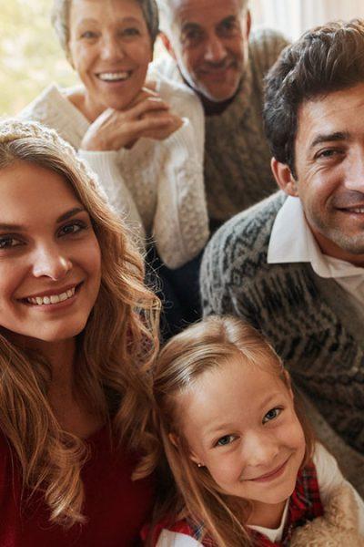 Mehr Gelassenheit, damit Weihnachten fröhlich werden - Selfie mit Oma, Opa, Eltern und Enkelkind neben dem Weihnachtsbaum