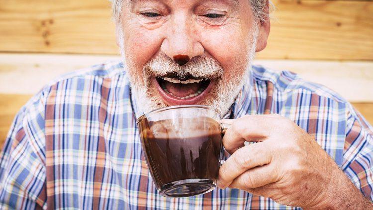 Egal wie gesund Schokolade ist - sie macht auf jeden Fall glücklich - Senior mit Trinkschokolade in der Hand, im Bart und an der Nasenspitze