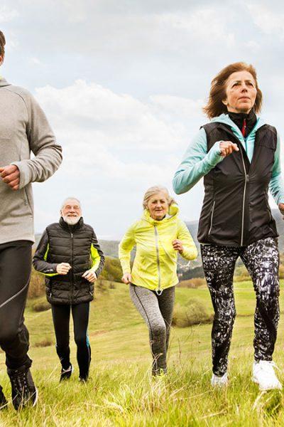 Wie Sport an der frischen Luft die Gesundheit fördert - Gruppe älterer Sportler beim Lauf querfeldein
